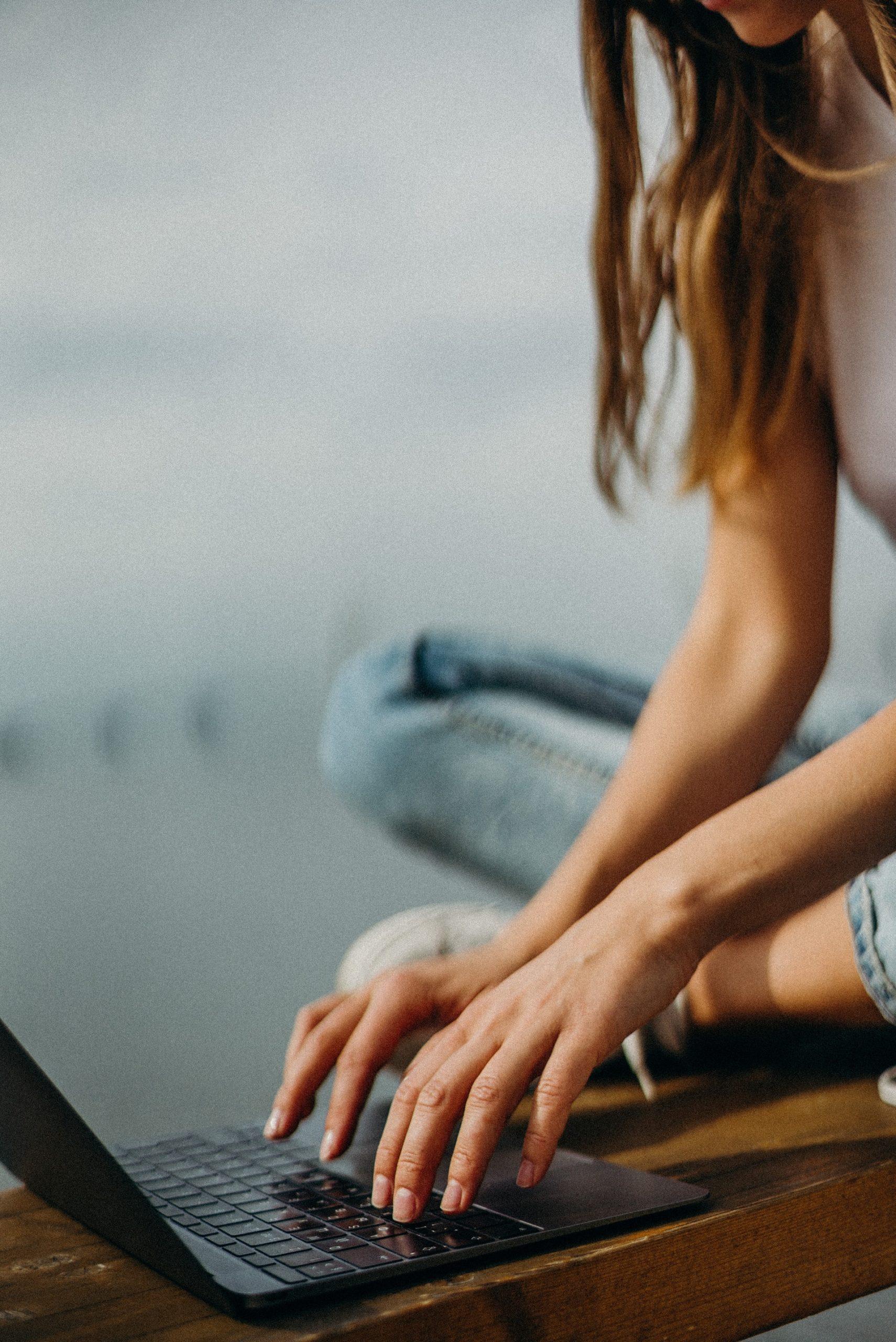 kvinna sitter med laptop och jobbar